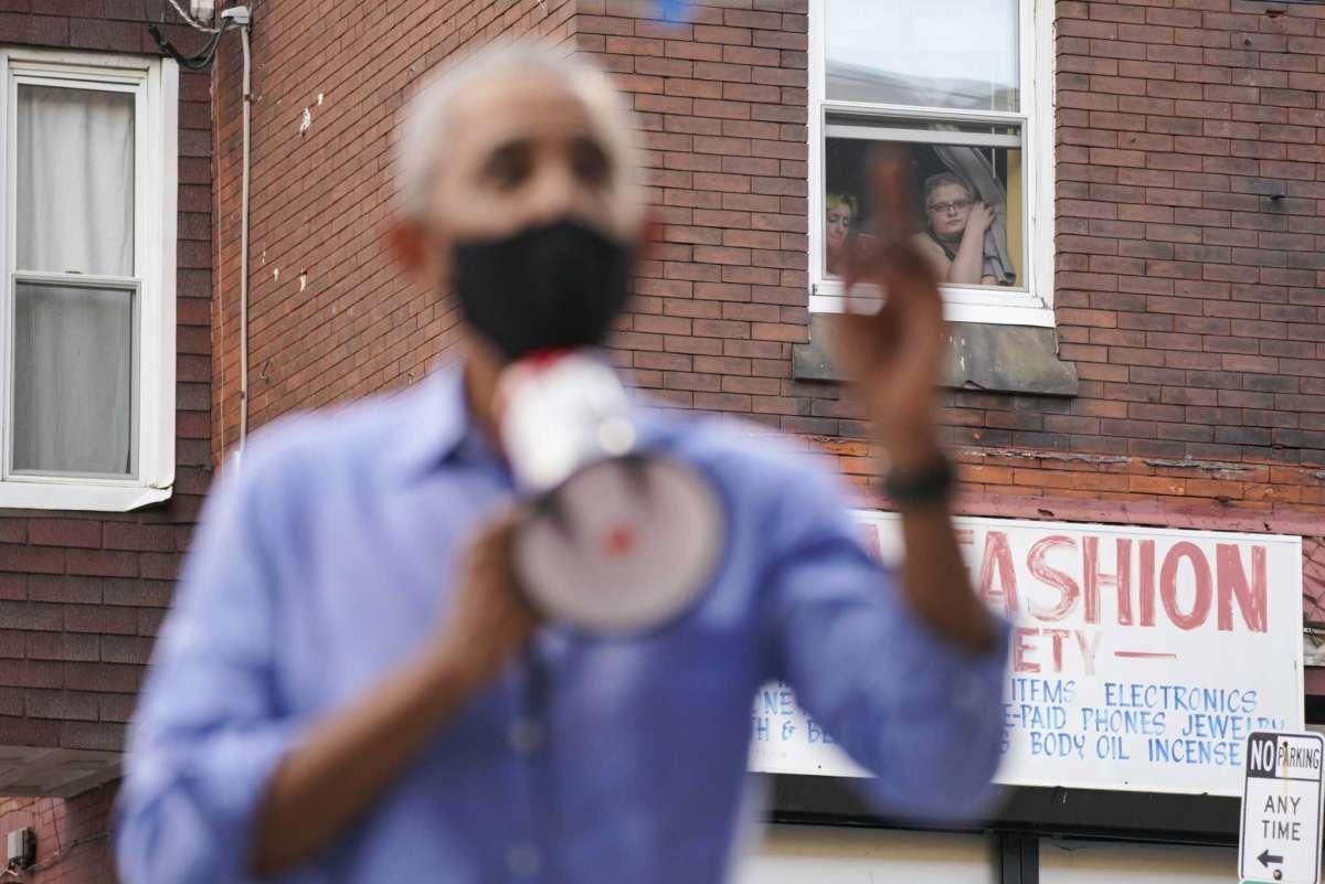 Women watch from a window as former president Barack Obama campaigns in Philadelphia on Wednesday for Democratic nominee Joe Biden.